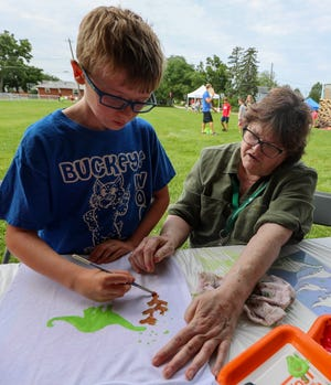 Grove City Arts Council volunteer Linda Lerum helps Camden Pfeiffer, 9, decorate a T-shirt during the Grove City EcoFest on Aug. 14.