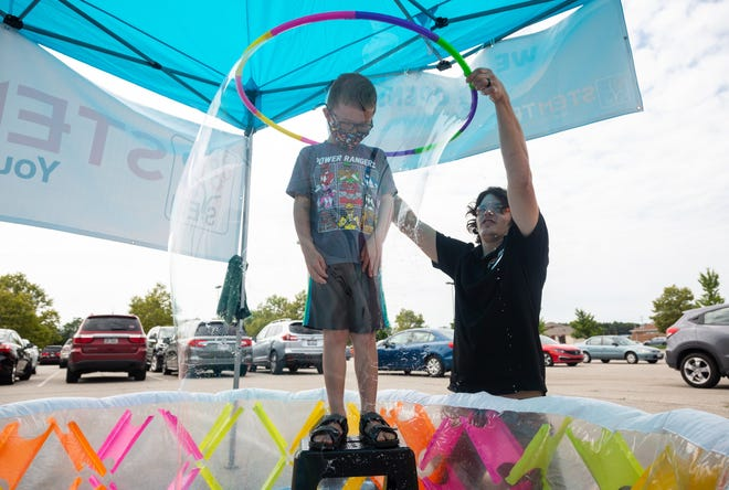 Teacher Matt Marsh conducts an activity that puts David Dailey, 7, of Marion in a bubble using a plastic hoop during an open house at Stemtree of Lewis Center, 6437 Pullman Drive, on Aug. 14.