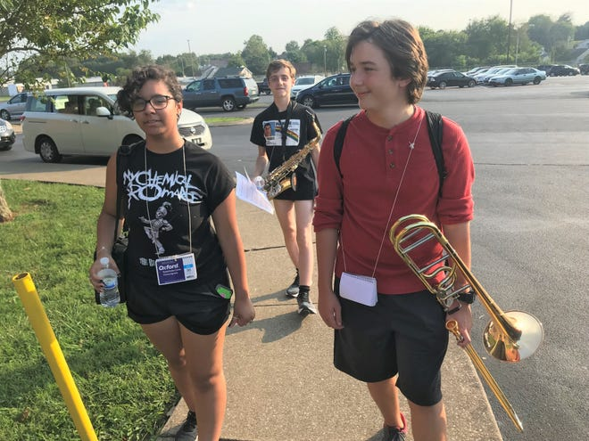 Spring Hill High School Marching Band members (left) Jaelyn Addison (clarinet), Luke Smith (trombone) and Jonathan Arnett (saxophone) file into the high school after band practice on August 5, 2021 in Spring Hill, Tenn. Because the high school has reached its capacity of 1,200 students, portables could be installed on the campus.