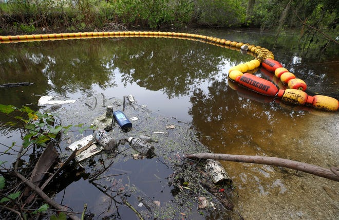 A water goat installed in a Holly Hill canal traps litter before reaching the river, Monday, August 16, 2021.