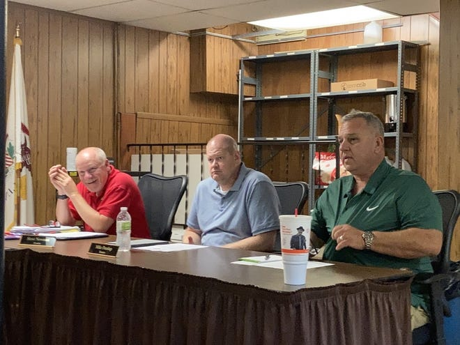 Jim Hickerson, right, was installed as the newest member of the Orion village board on Monday night, Aug. 16. He joins Steve Newman, left, and Mike Dunlap, center, as a trustee. Also on the board are Village President Jim Cooper and trustees Bob Mitton, Neal Nelson and Mel Drucker.