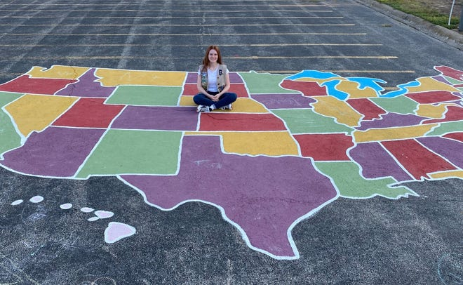 Sylvia Baumgardner sits in the middle of a mural at Southwest Elementary she did as part of her Gold Star project.