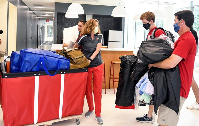 Indiana University President Pamela Whitten helps freshman Jackson Welp move his luggage to his dorm room in Walnut Grove Residence Hall during IU move-in day Aug 16. (Bobby Goddin/Herald-Times)