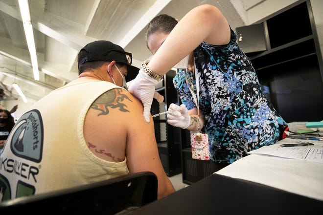 RN Leonor Esquivel administers a Covid-19 vaccine during a Polk County Health Department hold pop-up vaccine clinic held in the Vistor locker room at Bryant Stadium in Lakeland Fl. Tuesday August 17 2021.  ERNST PETERS/ THE LEDGER