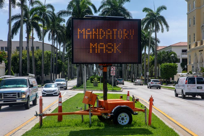 """Drivers entering Palm Beach over the Royal Park Bridge are greeted with a sign that says """"Mandatory Mask"""" in July 2020. The town brought back a mask mandate for all town property after the recent resurgence in COVID-19 infections."""