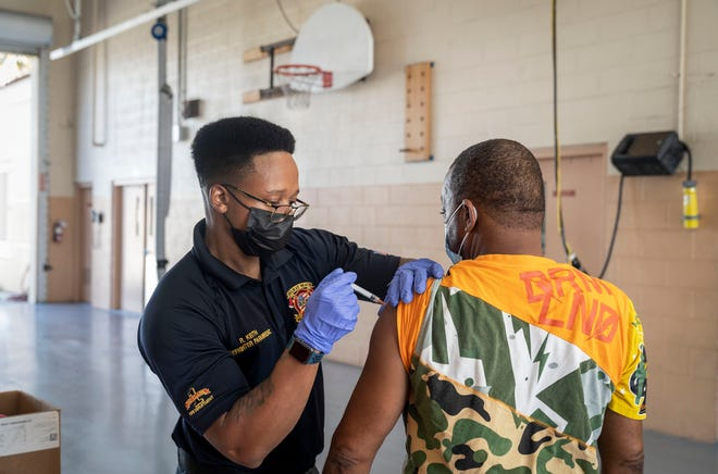 Firefighter Ray Keith administers a COVID-19 vaccination to man at the Delray Beach Fire Rescue station in Delray Beach, Florida on August 17, 2021.  The vaccines are free and available to the public every Tuesday from 9 a.m. to noon at 501 West Atlantic Ave. 23 people were vaccinated.
