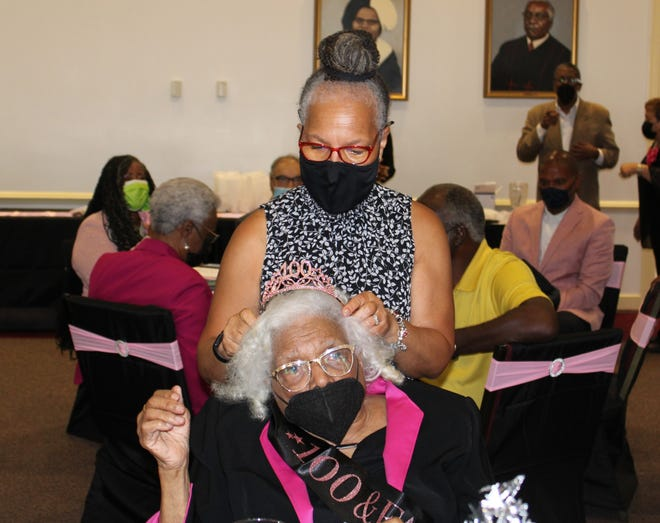 Debra Broadus adjusts her godmother Evelyn Watkins Jemison's birthday crown at the Tabernacle Baptist Church Community Life Center in Petersburg, Va. on Aug. 6, 2021.