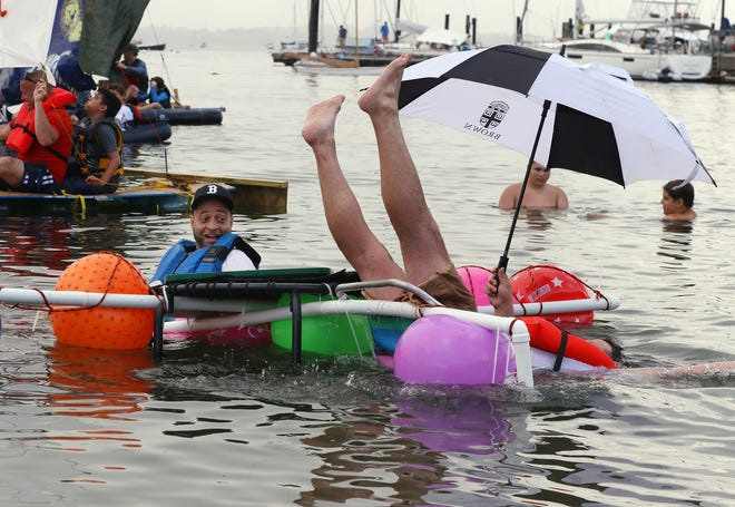 Steve Dos Santos, of North Providence, watches his partner Andrew Avery, of Providence, take a dip into the water as he falls out of his aluminum chair on their makeshift craft after losing their sail in the 43rd annual Jamestown Yacht Club Fools' Rules Regatta.