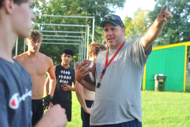 New North Smithfield/Mount St. Charles head football coach Jeff Paiva gives directions to a group of players at a workout Tuesday evening.