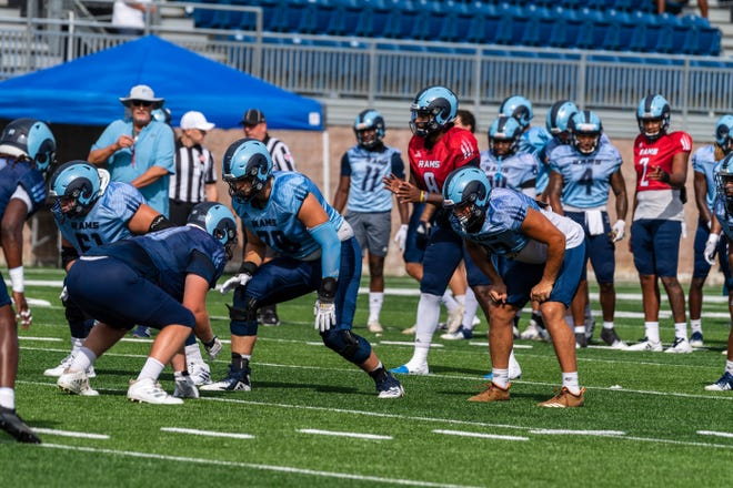 Quarterback Kasim Hill (8), a Tennessee transfer, prepares to take the snap at URI's scrimmage on Tuesday. Coach Jim Fleming (wearing hat) is in the background.