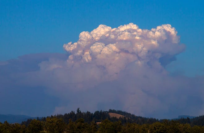A smoke plume rises from the Gales Fire east of Fall Creek as seen from Interstate 5 north of Creswell.