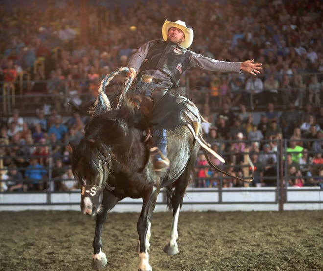 Ty Manke of Rapid City, SD participates in the saddle bronc riding event at Monday's portion of the Dacotah Stampede at the Brown County Fair. American News photo by Jenna Ortiz, 08/16/21.
