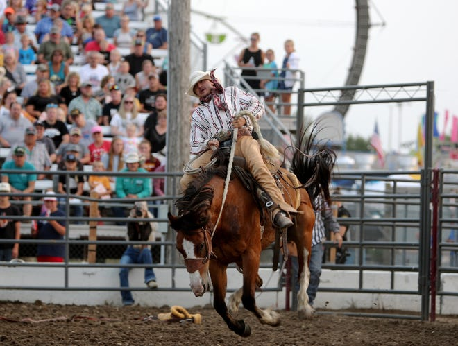 Straten Ducheneaux of Eagle Butte rides in the saddle bronc riding event during Monday night's session of the Dacotah Stampede at the Brown County Fair.