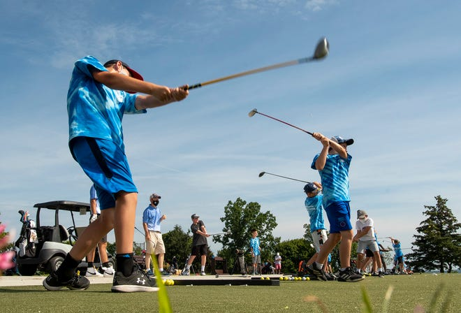 Children practice their swing on the driving range during the Danny Rossetti Junior Golf Camp Tuesday at Green Hill Golf Course.