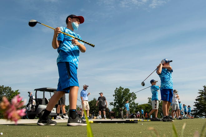 Youths practice their swings on the driving range during last week's Danny Rossetti Junior Golf Camp at Green Hill Municipal Golf Course.