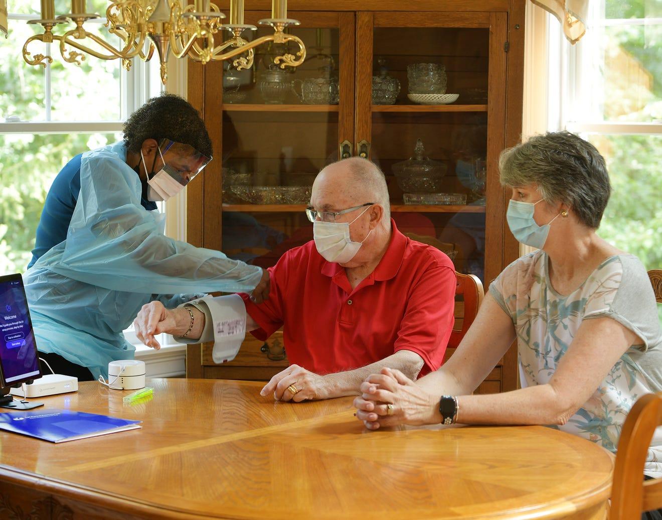 Nurses Lisa DeBoise adjusts the blood pressure cuff on Thad Stappenbeck with his wife Mary beside him. Christine Peterson/Telegram & Gazette