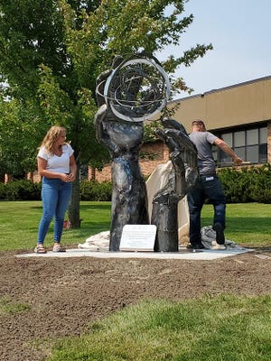 Tessa Holien unveils her sculpture on the campus  of Lake Area Technical College Tuesday afternoon.