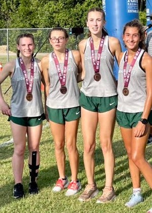 """The Waxahachie girls' cross-country """"A"""" relay team poses for a photo at the Timberview 6-Mile Relay in Mansfield on Saturday morning. Sophomore Emilee Jones (right) ran the fastest individual time in the girls' division."""