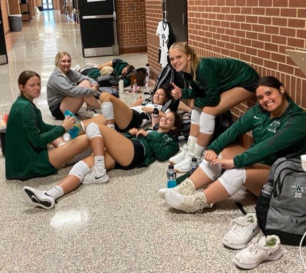 Waxahachie volleyball players chill out between matches at the Mansfield tournament on Friday. The Lady Indians won the Silver Bracket championship with a best-of-3-set victory over Midlothian on Saturday.