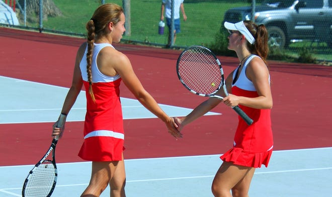 Two Wellington tennis players high five each other after a set