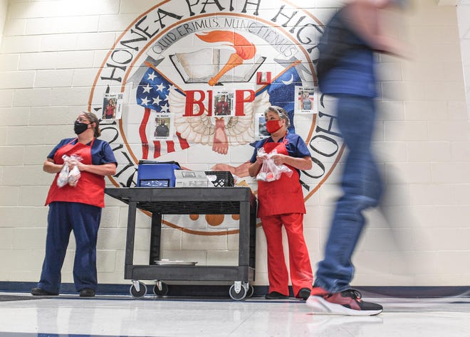 Tina Ellison, left, and Beverly Jones of the cafeteria offer breakfast items to students arriving on the first day of school at Belton Honea Path High School in Honea Path, S.C. Tuesday, August 17, 2021.