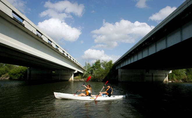 Megan Freund and Ryan Lumpp pass under the I-37 bridge Saturday, Oct. 23, 2010 as they make their way to the finish line at Labonte Park during the 2010 Corpus Christi Paddle Prix and Rally along the Nueces River in Corpus Christi.