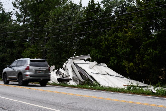 H2e construction workers clear debris that was blown off the roof of the strip mall located off New Neely Ferry Road in Mauldin Tuesday, Aug. 17, 2021.