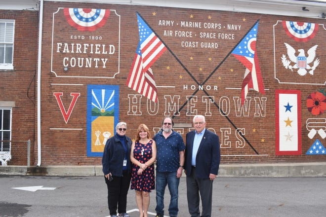 From left to right: Ohio Governor Mike DeWine's Military and Veteran Liason, Tammy Puff; Theresa Mecionis; Mecionis' fiance, Dan Fuller; and Fairfield County Commissioner Dave Levacy stand in front of Lancaster's new veterans mural on East Main St on Aug. 17, 2021. Mecionis's son Sgt. Joseph Collette died while serving in Afghanistan in 2019.