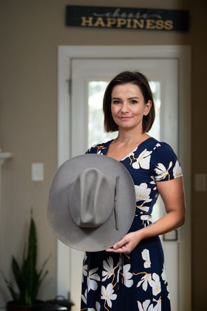 Bree Smith holds her dad's cowboy hat in her home in Hendersonville, Tenn., Tuesday, July 20, 2021. It's one of his things she chose to keep after he died from a drug overdose when she was 10