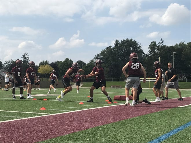 Seaholm runs quarterback and running back handoff drills in an afternoon practice while head coach Jim DeWald looks on.