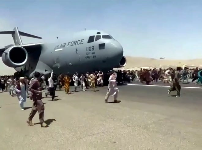 Hundreds of people run alongside a U.S. Air Force C-17 transport plane as it moves down a runway of the international airport in Kabul, Afghanistan, Monday, Aug.16. 2021. Thousands of Afghans have rushed onto the tarmac at the airport, some so desperate to escape the Taliban capture of their country that they held onto the American military jet as it took off and plunged to their deaths. (Verified UGC via AP)