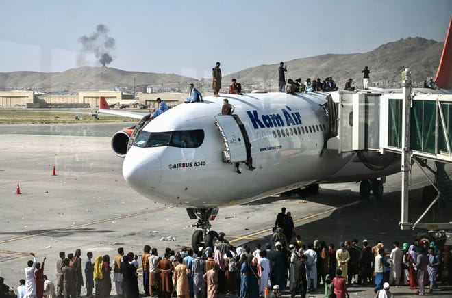 Afghan people climb atop a plane as they wait at the Kabul airport in Kabul on August 16, 2021, after a stunningly swift end to Afghanistan's 20-year war, as thousands of people mobbed the city's airport trying to flee the group's feared hardline brand of Islamist rule. (Wakil Kohsar/AFP via Getty Images/TNS)