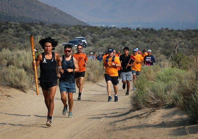 Ku Stevens leads a group of people on the Remembrance Run about five miles east of Carson City and the Stewart Indian School on Aug. 14, 2021. Stevens is seen holding the Peace and Dignity Journey's eagle staff.
