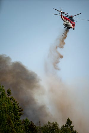 A helicopter drops fire retardant on a portion of the Greenwood Fire near Highway 2 as it moves northeast on Monday, Aug. 16, 2021, in Duluth, Minn. The wildfire has continued to grow and spread towards the northeast as firefighters battle the flames from both the ground and air. (Alex Kormann/Star Tribune via AP)