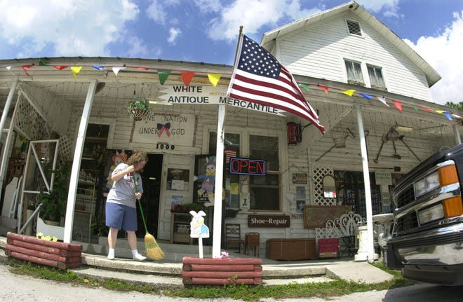 Cathy Wells, owner of the White City Historical Antique Mercantile business inside the old Mercantile Store, sweeps off the front porch of the White City landmark building built in 1901 along Midway Road in White City in March 2003.