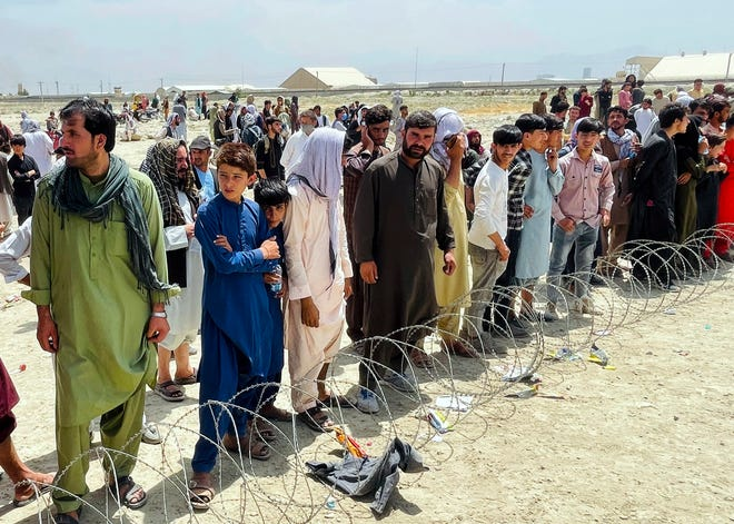 """Hundreds of people gather outside the international airport in Kabul, Afghanistan, on Aug. 17. The Taliban declared an """"amnesty"""" across Afghanistan and urged women to join their government, seeking to convince a wary population that they have changed as desperate crowds tried to flee the country."""
