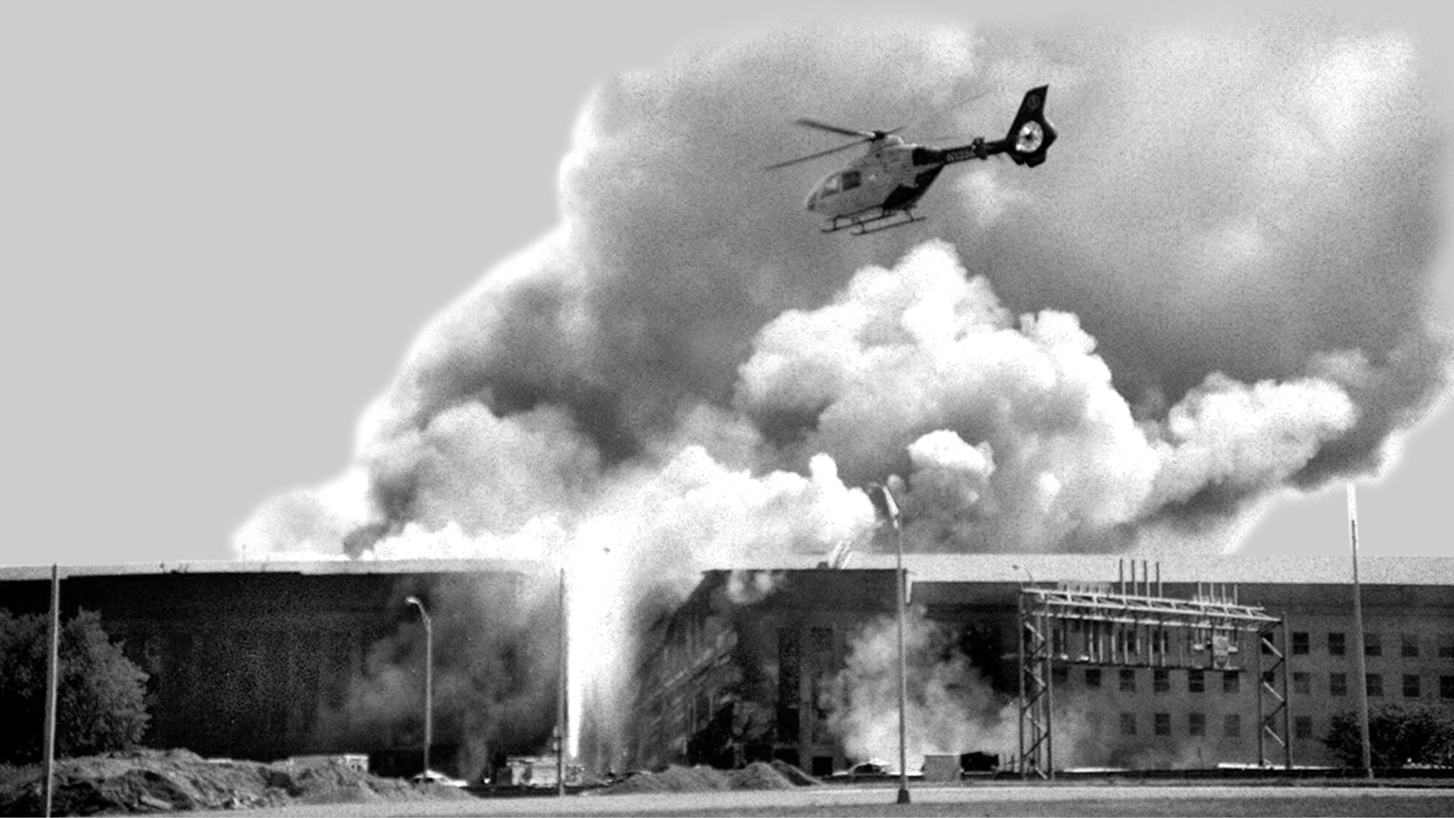 A helicopter flies over the Pentagon in Washington as smoke billows over the building, after being hit by Flight 77.