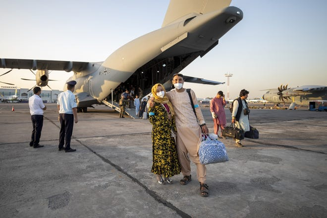People evacuated from Afghanistan pose in front of a German Bundeswehr airplane after arriving at the airport in Tashkent, Uzbekistan, Tuesday.