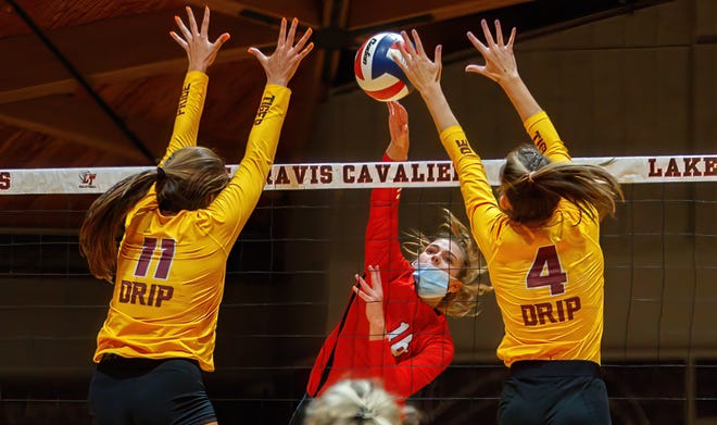 Lake Travis outside hitter Brooke Davis splits a pair of Dripping Springs blockers during the third set at the nondistrict volleyball game Tuesday at Lake Travis High School. Davis helped the Cavs to a 3-0 win.