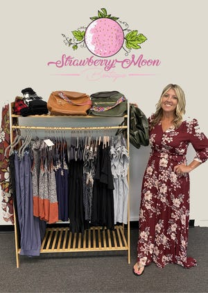 Sarah Coyne, the owner of Strawberry Moon Boutique in Twinsburg, stands with a sampling of what the boutique offers.