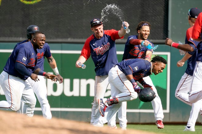 Minnesota Twins' Jorge Polanco, right, tries to evade a water shower after his bases-loaded, walkout single drove in the winning run in the 11th inning as the Twins beat Cleveland 8-7 in a baseball game, Wednesday, Aug. 18, 2021, in Minneapolis. (AP Photo/Jim Mone)