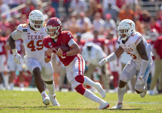 Oklahoma Sooners quarterback Spencer Rattler (7) looks for room to run against Texas Longhorns defensive lineman Ta'Quon Graham (49) and Texas Longhorns defensive back D'Shawn Jamison (5) and  in an NCAA college football game at the Cotton Bowl in Dallas.