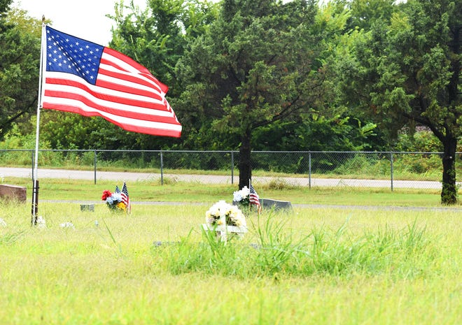An American flag flies among graves at Rose Hill Cemetery while some markers are hidden behind tall grass Wednesday, Aug. 18, 2021. The parks department has struggled to find seasonal help this summer to help maintain the city cemeteries.