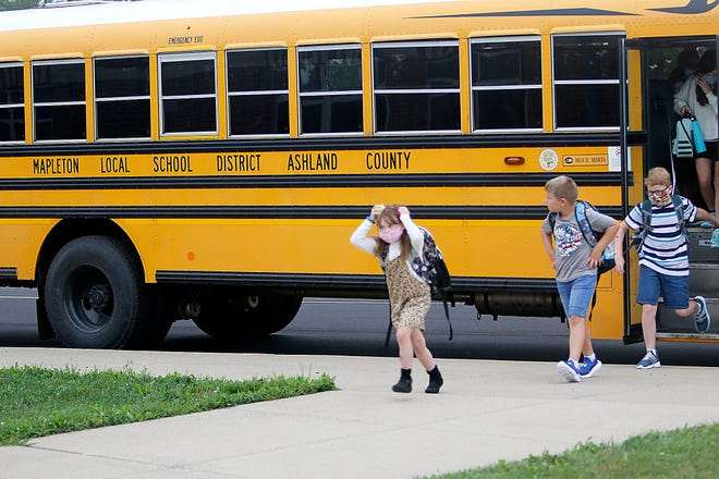 Students exit the bus as they arrive at Mapleton Elementary for the first day of school on Wednesday.
