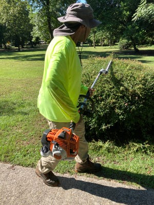 Leonard Vann, a part-time employee of Augusta Parks and Recreation, trims a bush at Pendleton King Park on Wednesday, Aug. 18. 2021