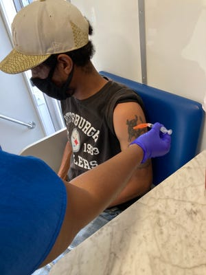 Rasheed Ward, 45, gets a second dose of the COVID-19 vaccine in a mobile clinic run by Medical Associates Plus during a visit to Olmstead Homes public housing in Augusta in August.