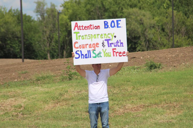 Scott Moll holding up a sign outside Andover High School during protest