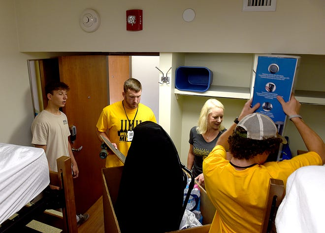 Salt Company college ministry of Anthem Church volunteers Ryan Karg, center, and Than Drage, right, help MU freshman David Maller, 18, and his mother, Juliana, of St. Charles, Ill., move Maller into his dorm room in Wolpers Hall on Wednesday.