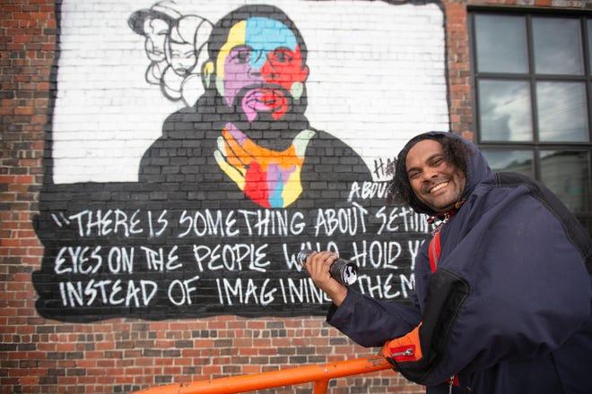 Local artist Bryan Moss works on a mural featuring Hanif Abdurraqib along East Main Street