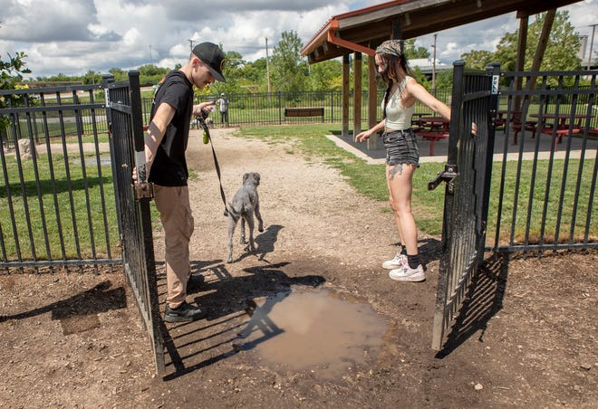 Tyler Williams and Gill Yobbi close the gate behind them as they navigate around a mud puddle at the entrance of the large dog play area at the Scioto Audubon Dog Park. The new dog park will feature artificial turf with a drainage system.
